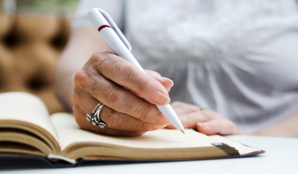 Woman writes about her day to enjoy the health benefits of journaling.